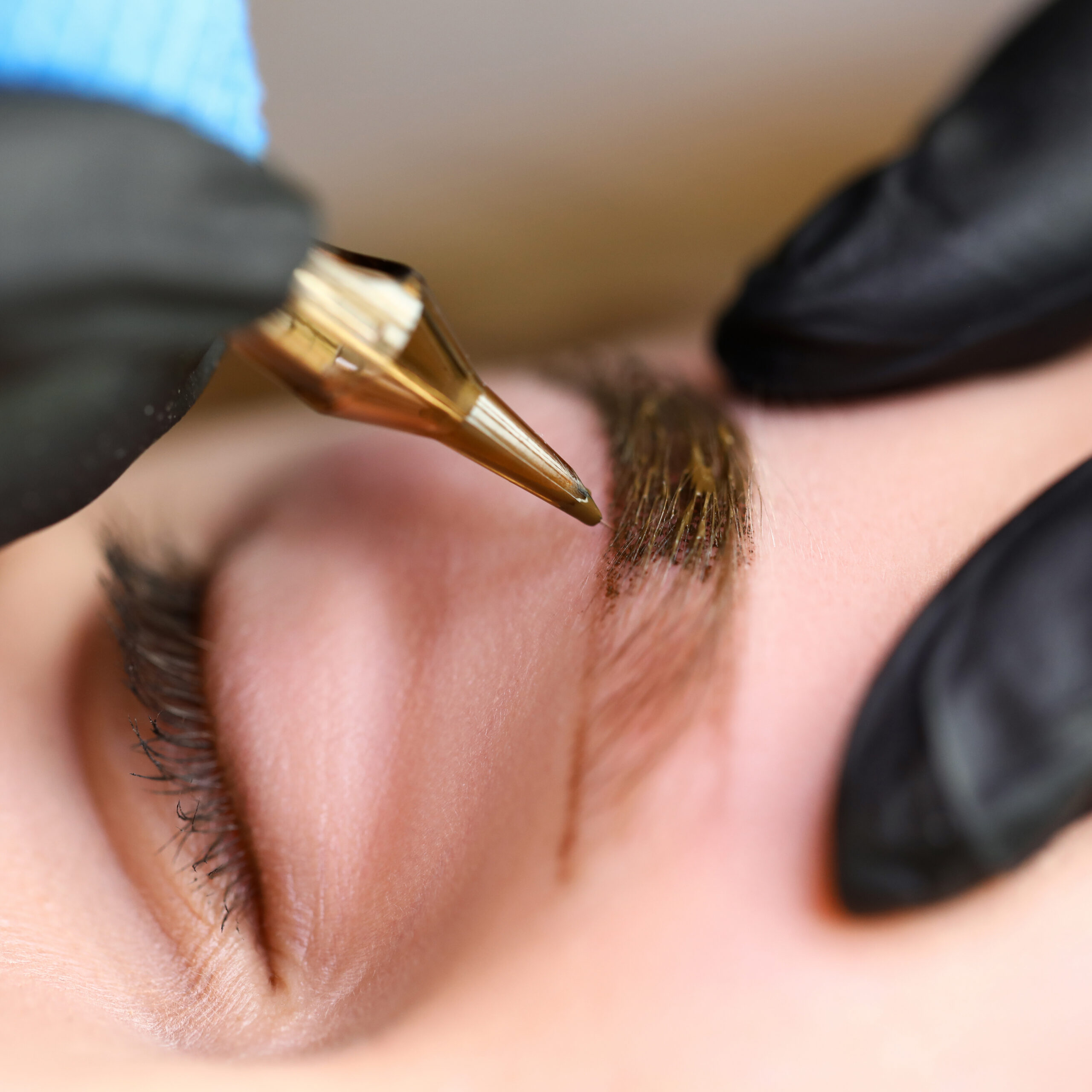Beauty masters hands do permanent eyebrow makeup. Minimal trauma to skin. Eyebrow microblading is performed using manipulator handle and special nozzle with needles. Cosmetologist skill level